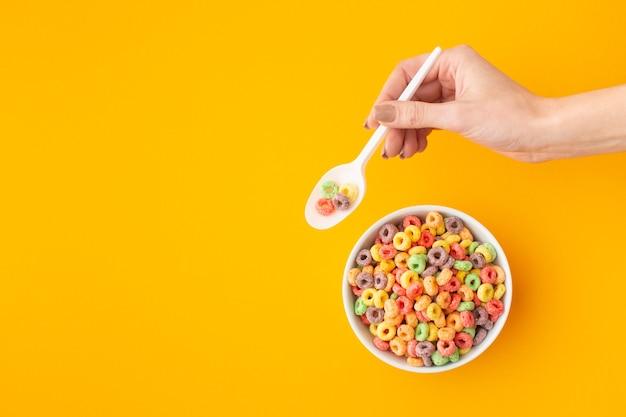 Mano che tiene il cucchiaio di plastica con cereali