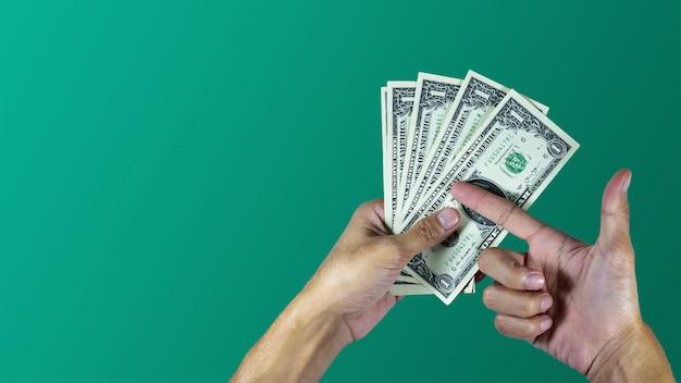 Mano che tiene il disegno del dollaro su sfondo verde