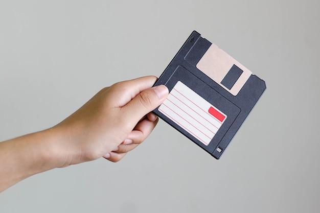 Mano che tiene il floppy disk nero
