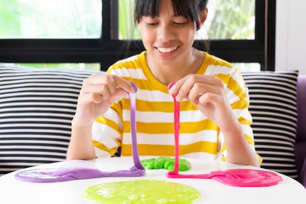 Mano che tiene il giocattolo chiamato slime, fratello e sorella di sibling divertendosi ed essendo creativi