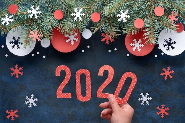 Mano che tiene il numero 2020, natale con ramoscelli di abete decorato su oscurità
