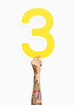Mano che tiene il numero 3