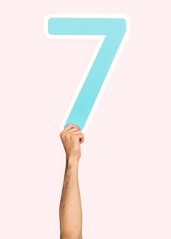 Mano che tiene il numero 7