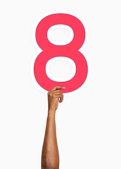 Mano che tiene il numero otto segno
