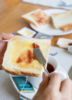 Mano che tiene il pane con marmellata di frutta e tazza di tè