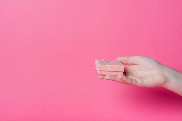 Mano che tiene il piccolo contenitore di regalo su sfondo rosa