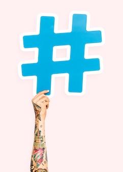 Mano che tiene il simbolo hashtag