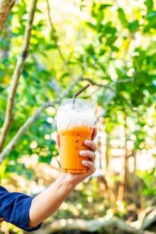 Mano che tiene il tè freddo al latte tailandese