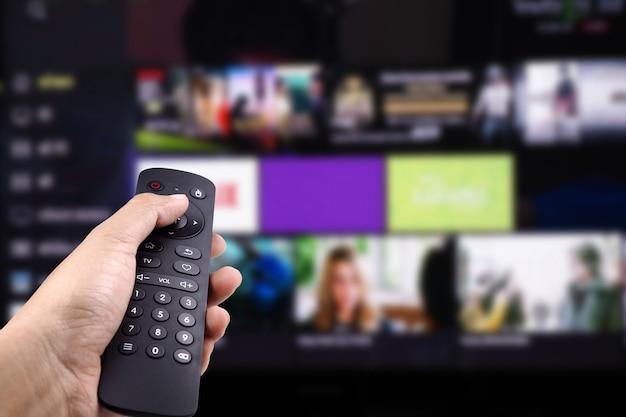 Mano che tiene il telecomando della tv con smart tv