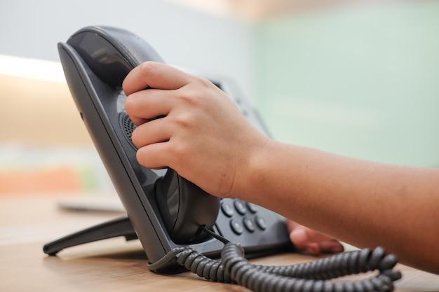 Mano che tiene il telefono dell'altoparlante per parlare