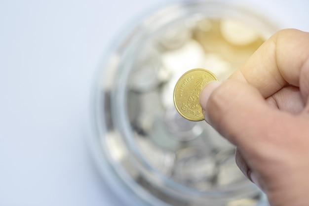 Mano che tiene inserto di monete d'oro per monete bottiglia di vetro. concetto di risparmio di denaro.
