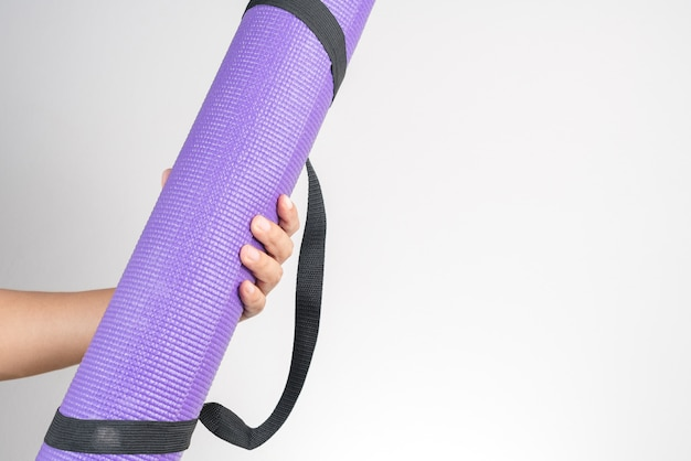 Mano che tiene l'accessorio per tappetino yoga, esercizio fisico e fitness