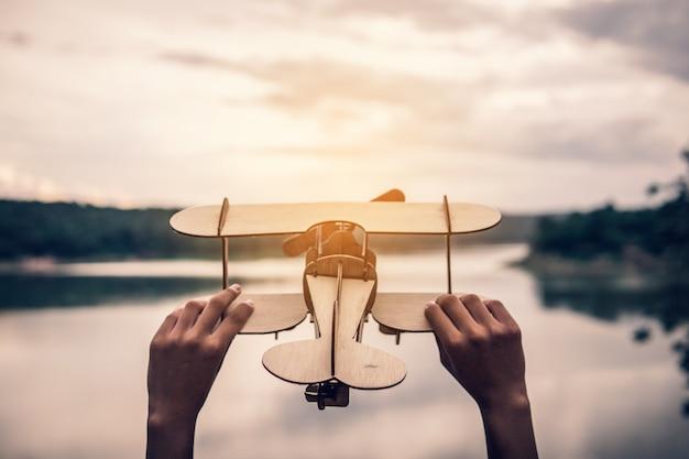 Mano che tiene l'aeroplano di legno nel natur