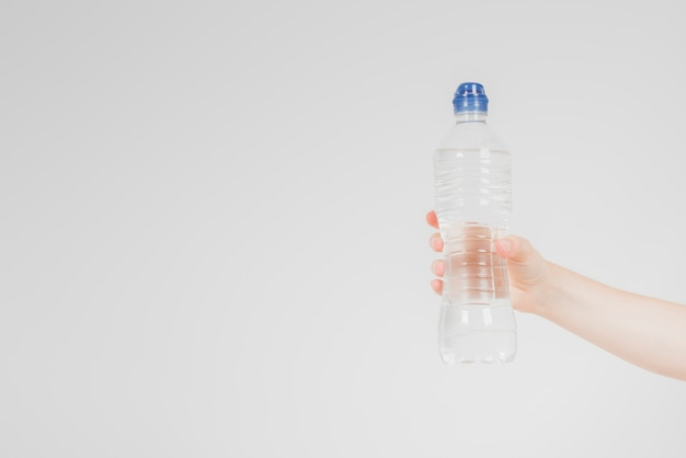 Mano che tiene la bottiglia d'acqua
