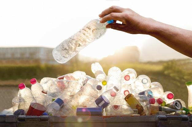 Mano che tiene la bottiglia di plastica riciclabile nel bidone della spazzatura