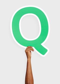 Mano che tiene la lettera q
