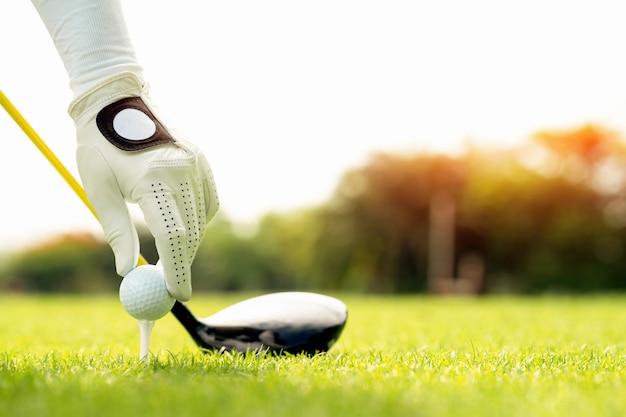 Mano che tiene la pallina da golf con il tee sul percorso, tee off, copia spazio sul lato destro