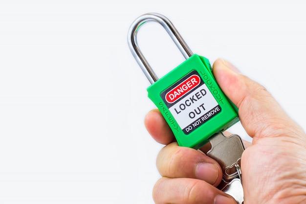 Mano che tiene la serratura verde con chiave