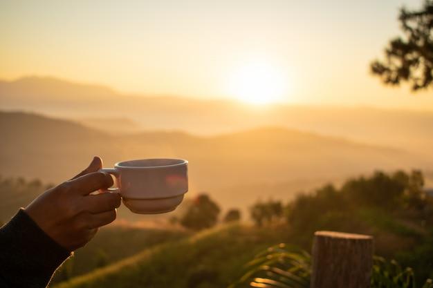 Mano che tiene la tazza di caffè con vista sulle montagne e l'alba del mattino