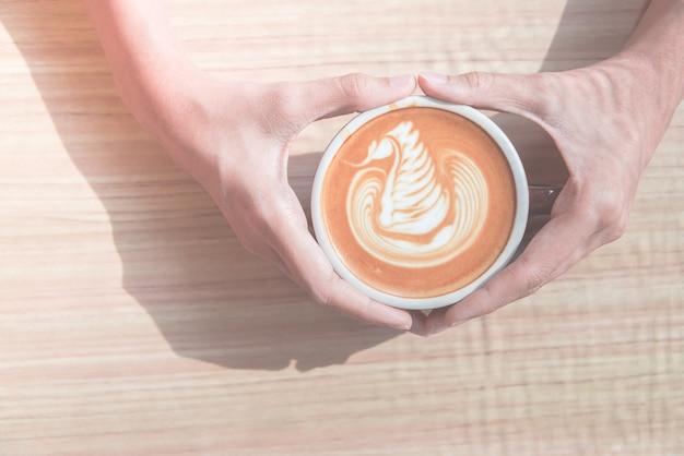 Mano che tiene la tazza di caffè