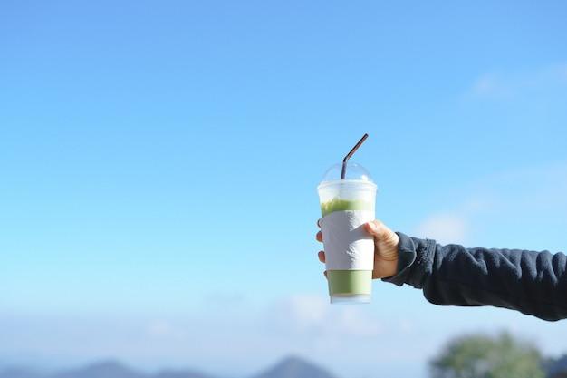 Mano che tiene la tazza di tè verde ghiacciato
