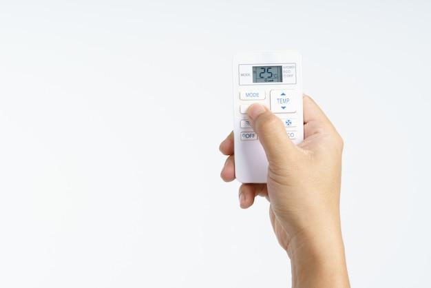 Mano che tiene la temperatura impostata a distanza del condizionatore d'aria a 25 gradi centigradi