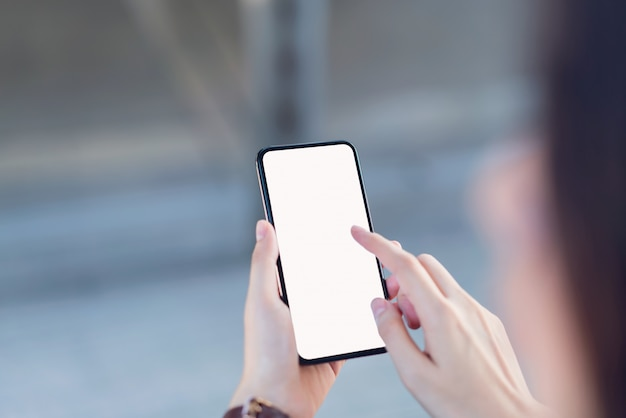 Mano che tiene lo schermo in bianco dello smartphone