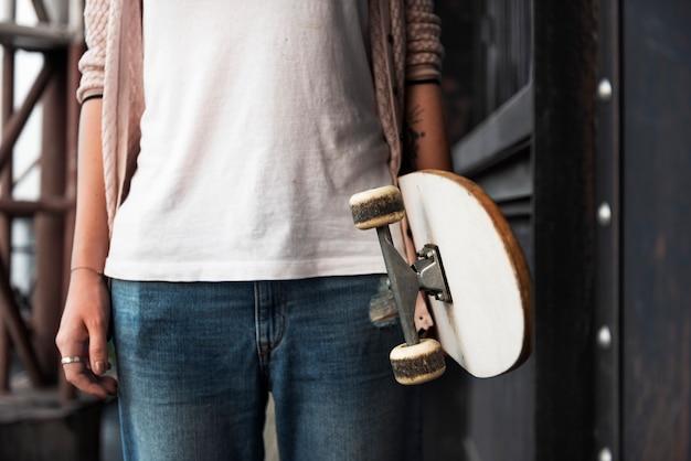 Mano che tiene lo skateboard