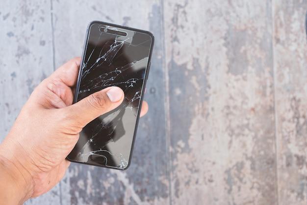 Mano che tiene lo smartphone rotto