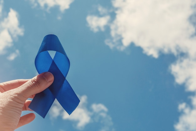 Mano che tiene nastro blu, consapevolezza del cancro alla prostata, consapevolezza della salute degli uomini, movember, giornata internazionale degli uomini, giornata mondiale del diabete