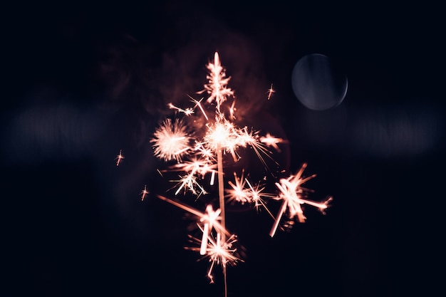 Mano che tiene scoppiettante sparkler su uno sfondo nero durante la notte