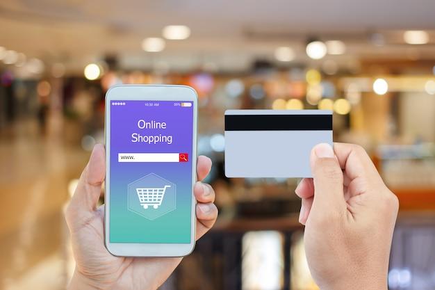 Mano che tiene smart phone con lo shopping online su schermo e carta di credito