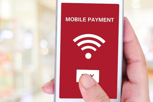 Mano che tiene smart phone con pagamento mobile sullo schermo