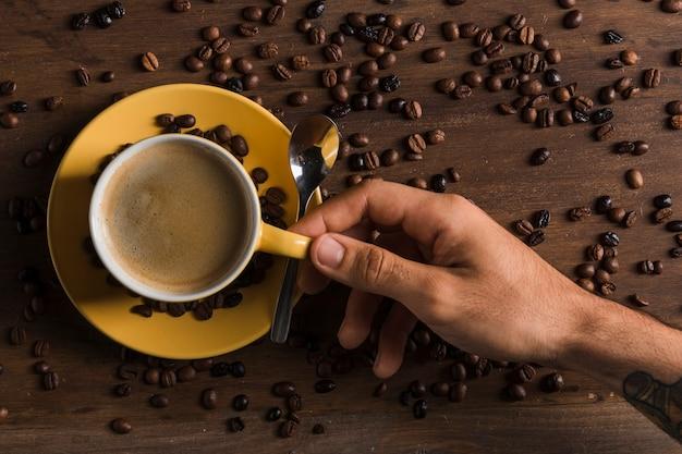 Mano che tiene tazza con caffè vicino piatto
