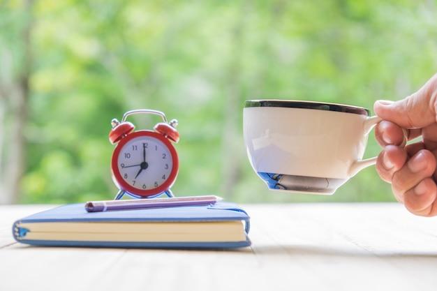 Mano che tiene tazza di caffè bianco taccuino, penna, sveglia su sfondo naturale