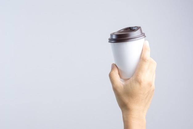 Mano che tiene tazza di caffè caldo