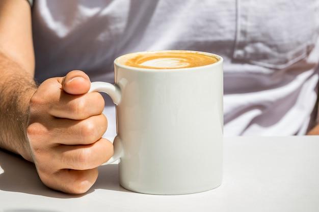 Mano che tiene tazza di caffè