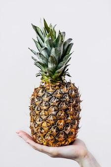 Mano che tiene un ananas