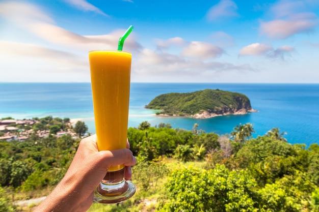 Mano che tiene un bicchiere di succo su koh phangan island, thailandia