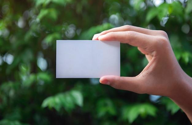 Mano che tiene un biglietto da visita bianco testo vuoto sullo sfondo della natura