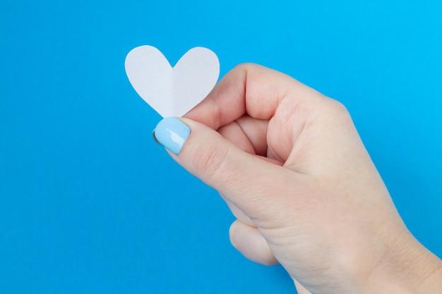 Mano che tiene un cuore bianco su sfondo blu. sfondo per san valentino