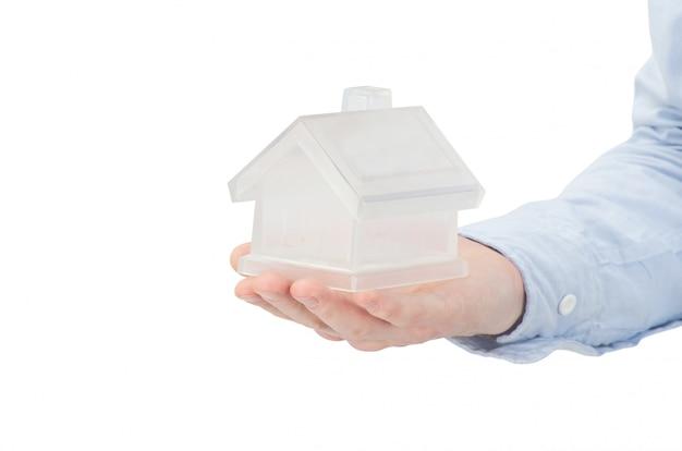 Mano che tiene un giocattolo di casa. concetto di agente immobiliare