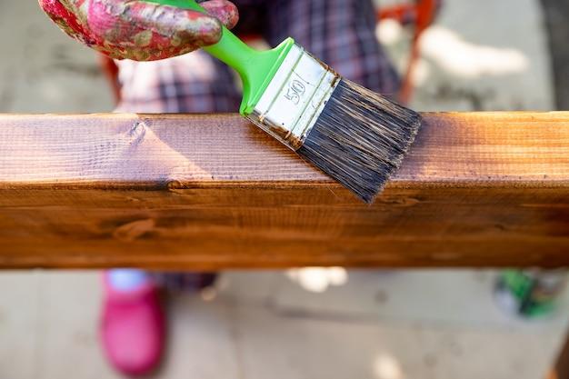 Mano che tiene un pennello che applica vernice vernice su una superficie di legno