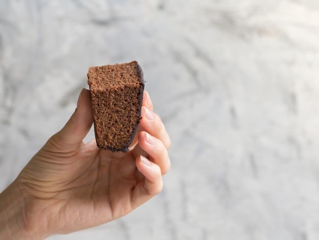 Mano che tiene un pezzo di brownie appena sfornato
