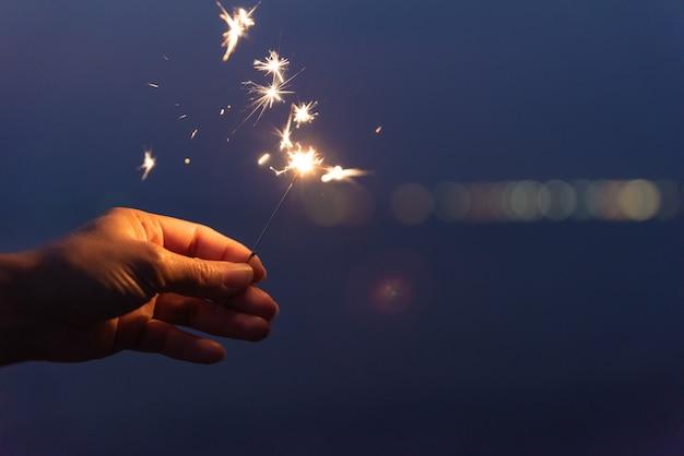 Mano che tiene un sparkler sulla spiaggia durante il tramonto. concetto di celebrazione