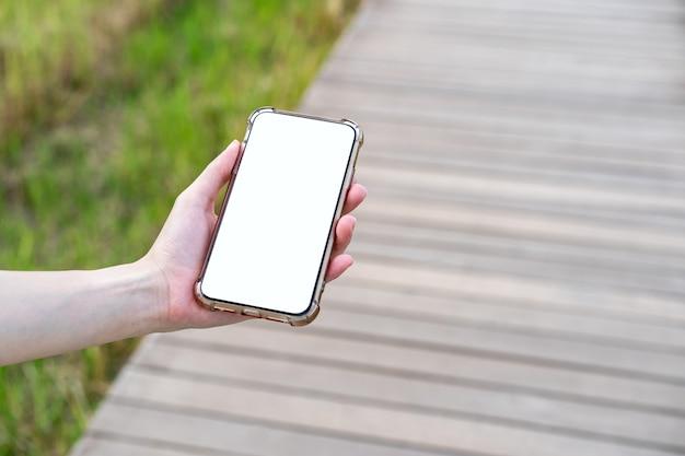 Mano che tiene un telefono cellulare con schermo mockup bianco in modo a piedi ponte di legno.