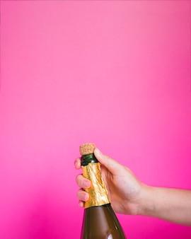 Mano che tiene una bottiglia di champagne