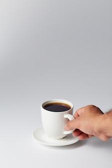 Mano che tiene una tazza di caffè bianca