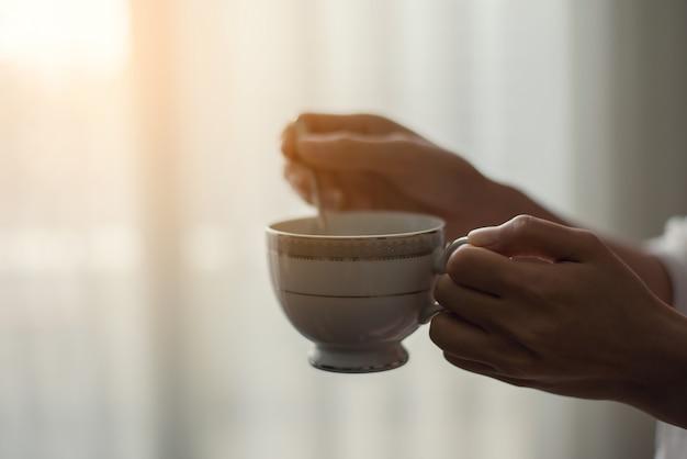 Mano che tiene una tazza di caffè e utilizzare un cucchiaio da caffè