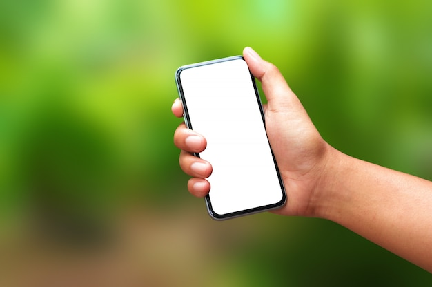 Mano che tiene uno smartphone e uno schermo vuoto.